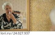 Купить «Пожилая женщина красит губы», видеоролик № 24027937, снято 28 октября 2016 г. (c) Илья Шаматура / Фотобанк Лори