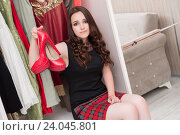 Купить «Young woman choosing clothing for evening party», фото № 24045801, снято 31 августа 2016 г. (c) Elnur / Фотобанк Лори