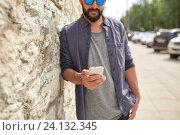 Купить «close up of man with smartphone at stone wall», фото № 24132345, снято 2 июня 2016 г. (c) Syda Productions / Фотобанк Лори
