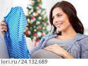 Купить «happy woman holding baby boys bodysuit at home», фото № 24132689, снято 23 марта 2016 г. (c) Syda Productions / Фотобанк Лори