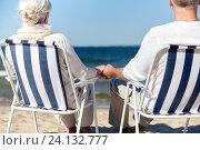 Купить «senior couple sitting on chairs at summer beach», фото № 24132777, снято 18 августа 2015 г. (c) Syda Productions / Фотобанк Лори