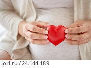 Купить «close up of pregnant woman with red heart», фото № 24144189, снято 20 мая 2016 г. (c) Syda Productions / Фотобанк Лори