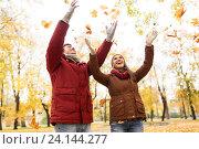 Купить «happy young couple throwing autumn leaves in park», фото № 24144277, снято 9 октября 2016 г. (c) Syda Productions / Фотобанк Лори