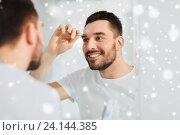 Купить «man with tweezers tweezing eyebrow at bathroom», фото № 24144385, снято 15 января 2016 г. (c) Syda Productions / Фотобанк Лори