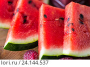 Купить «close up of watermelon slices on wooden table», фото № 24144537, снято 5 августа 2016 г. (c) Syda Productions / Фотобанк Лори