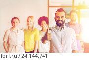 Купить «happy man showing thumbs up over team in office», фото № 24144741, снято 29 марта 2015 г. (c) Syda Productions / Фотобанк Лори