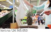 Купить «woman weighing pineapple on scale at grocery store», видеоролик № 24165053, снято 3 ноября 2016 г. (c) Syda Productions / Фотобанк Лори