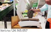 Купить «woman weighing pineapple on scale at grocery store», видеоролик № 24165057, снято 3 ноября 2016 г. (c) Syda Productions / Фотобанк Лори