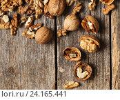 Купить «Walnut kernels and whole walnuts on rustic old wooden table», фото № 24165441, снято 14 февраля 2016 г. (c) Майя Крученкова / Фотобанк Лори