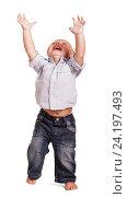 Купить «Веселый босой мальчик стоит на белом фоне и тянется руками вверх», фото № 24197493, снято 12 августа 2016 г. (c) Сергей Молодиков / Фотобанк Лори