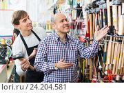 Купить «Ordinary positive smiling customer and seller choosing hammer», фото № 24204581, снято 18 ноября 2018 г. (c) Яков Филимонов / Фотобанк Лори