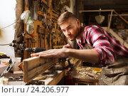 Купить «carpenter working with wood plank at workshop», фото № 24206977, снято 14 мая 2016 г. (c) Syda Productions / Фотобанк Лори
