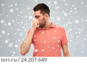 sick man with paper wipe blowing nose over snow. Стоковое фото, фотограф Syda Productions / Фотобанк Лори