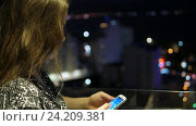 Pretty young girl standing on balcony and using touchscreen cellphone. Blurred night city view with beautifull bokeh in the background. Стоковое видео, видеограф Павел Котельников / Фотобанк Лори