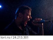 Купить «Молодой эмоциональный мужчина громко поет в микрофон в сценическом свете», фото № 24213301, снято 3 сентября 2016 г. (c) Pavel Biryukov / Фотобанк Лори