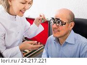 Купить «Adult specialist examinating eyesight», фото № 24217221, снято 20 июля 2018 г. (c) Яков Филимонов / Фотобанк Лори