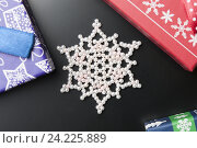 Снежинка из бусин на темном фоне с Новогодними коробочками. Стоковое фото, фотограф Владимир Булгаков / Фотобанк Лори