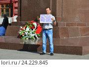 Купить «Мужчина держит плакат с надписью «Война - всего лишь трусливое бегство от проблем мирного времени» около памятника маршалу Жукову в Москве», эксклюзивное фото № 24229845, снято 9 июля 2016 г. (c) lana1501 / Фотобанк Лори