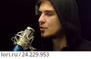 Купить «Молодой человек в капюшоне поёт у микрофона», видеоролик № 24229953, снято 5 октября 2016 г. (c) Pavel Biryukov / Фотобанк Лори