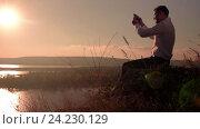 Купить «Мужчина фотографирует водный пейзаж на смартфон, сидя на вершине горы», видеоролик № 24230129, снято 5 октября 2016 г. (c) Pavel Biryukov / Фотобанк Лори