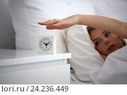 Купить «close up of woman with alarm clock in bed at home», фото № 24236449, снято 30 апреля 2016 г. (c) Syda Productions / Фотобанк Лори
