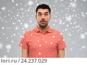 Купить «surprised man in polo t-shirt over snow background», фото № 24237029, снято 15 января 2016 г. (c) Syda Productions / Фотобанк Лори