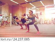 Купить «young man and woman training with barbell in gym», фото № 24237085, снято 30 ноября 2014 г. (c) Syda Productions / Фотобанк Лори