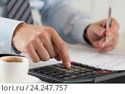 Купить «Мужчина держит в руке ручке и нажимает пальцем на кнопку калькулятора», фото № 24247757, снято 6 апреля 2016 г. (c) Людмила Дутко / Фотобанк Лори