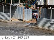 Купить «Рабочий очищает от грязи участок дороги при выезде со строительной площадки с помощью минимойки высокого давления», фото № 24263289, снято 7 июля 2015 г. (c) Юлия Олейник / Фотобанк Лори