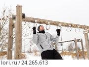 Купить «young man exercising on horizontal bar in winter», фото № 24265613, снято 10 ноября 2016 г. (c) Syda Productions / Фотобанк Лори