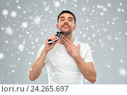 Купить «smiling man shaving beard with trimmer over snow», фото № 24265697, снято 15 января 2016 г. (c) Syda Productions / Фотобанк Лори