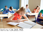 student girl with book writing school test. Стоковое фото, фотограф Syda Productions / Фотобанк Лори