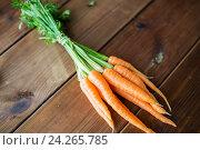 Купить «close up of carrot bunch on wooden table», фото № 24265785, снято 5 августа 2016 г. (c) Syda Productions / Фотобанк Лори