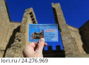 Билет в музей в руке на фоне Судакской крепости. Судак, Крым (2016 год). Редакционное фото, фотограф Яна Королёва / Фотобанк Лори
