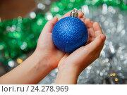 Купить «Синяя елочная игрушка шар в руках», фото № 24278969, снято 13 ноября 2016 г. (c) Иван Карпов / Фотобанк Лори