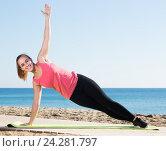 Charming girl exercising on exercise mat outdoor. Стоковое фото, фотограф Яков Филимонов / Фотобанк Лори