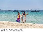 Три молодые вьетнамские девушки делают селфи на песчаном пляже на берегу Южно-Китайского моря. Вьетнам, DocLet Beach Resort (2016 год). Редакционное фото, фотограф Владимир Сергеев / Фотобанк Лори