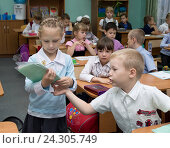 Ученица раздает тетради в начале урока (2015 год). Редакционное фото, фотограф Вячеслав Палес / Фотобанк Лори