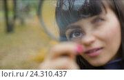 Купить «Женщина смотрит через лупу», видеоролик № 24310437, снято 7 января 2005 г. (c) Илья Шаматура / Фотобанк Лори