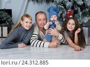 Купить «Счастливые родители и дети рядом с новогодней елкой», фото № 24312885, снято 9 декабря 2015 г. (c) Рустам Шигапов / Фотобанк Лори