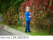 Мальчик стоит около забора с красными листьями. Стоковое фото, фотограф Елена Ганненко / Фотобанк Лори