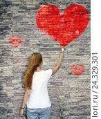 Молодая девушка рисует красное сердце на каменной стене. Стоковое фото, фотограф Бережная Татьяна / Фотобанк Лори