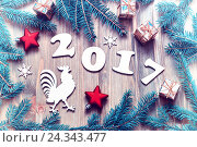 Купить «Happy New Year 2017 background with 2017 figures,Christmas toys, fir tree branches and rooster- New Year 2017 symbol. Vintage tones applied», фото № 24343477, снято 29 ноября 2016 г. (c) Зезелина Марина / Фотобанк Лори
