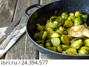 Купить «Pan-fried Brussels sprouts in cast-iron frying pan on wooden table», фото № 24394577, снято 24 сентября 2018 г. (c) mauritius images / Фотобанк Лори