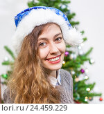 Купить «Портрет молодой красивой улыбающейся девушки в новогоднем колпаке», фото № 24459229, снято 28 декабря 2014 г. (c) Кекяляйнен Андрей / Фотобанк Лори
