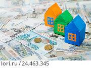 Купить «Три разноцветных бумажных дома на фоне денег», фото № 24463345, снято 9 декабря 2016 г. (c) Наталья Осипова / Фотобанк Лори