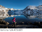 A woman walks past the holy lake of Gosainkund in the Langtang region, Himalayas, Nepal, Asia. Стоковое фото, фотограф Alex Treadway / age Fotostock / Фотобанк Лори