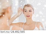 Купить «woman with tweezers tweezing eyebrow at bathroom», фото № 24492565, снято 13 февраля 2016 г. (c) Syda Productions / Фотобанк Лори