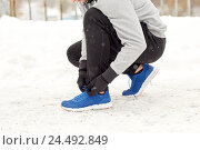 Купить «man with earphones tying sports shoes in winter», фото № 24492849, снято 10 ноября 2016 г. (c) Syda Productions / Фотобанк Лори