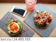 Купить «goat cheese and ham salads with smartphone at cafe», фото № 24493193, снято 22 сентября 2016 г. (c) Syda Productions / Фотобанк Лори